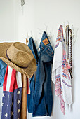 Straw hat, Stars-and-Stripes scarf and clothing hung from rack made from white-painted antlers