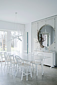 30s designer chairs around dining table and exposed concrete partition with round opening in white dining room