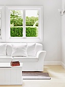 Simple, white wooden coffee table and sofa with white upholstery below window with view of garden