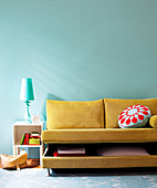 Gelbbeiges Schlafsofa mit halb geöffnetem Bettkasten in komplementärer Farbgebung zu Tischlampe und Wandfarbe