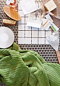 White patterned tiles and scraper next to toiletries and a green hand towel on a mosaic tile floor