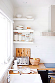 White sink, wooden worksurface and white wall-mounted shelves in kitchen