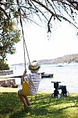 Summer idyll with back view of boy on swing; toddler's scooter and view of lake in blurred background