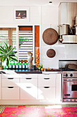 White kitchen with stainless steel appliances, glass splashback and colourful rug