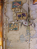 Coloured prints of various types of flower hanging on vintage wall with peeling paint
