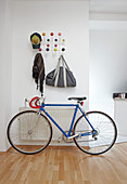 Coat rack made of white wire with colourful spherical hooks above racing bike in open-plan, modern hallway