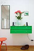 Knallgrüne Hängekommode mit Schubladen und hoher Spiegel an einer Dielenwand