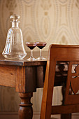 Antique glass decanter and glasses on wooden table and partially visible chair with carved back