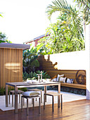 Stylish, sunny courtyard - modern terrace table and matching stools on floor with white tiles and wooden decking