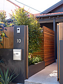 Dark grey garden wall with open gate and view of wooden screen in front of house