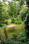 Garden table on lawn of wild garden