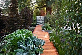Garden path made from recycled building timer leading to pond with water tank in background
