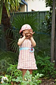 Little girl showing hands dirtied by gardening