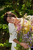 Woman holding armful of meadow flowers