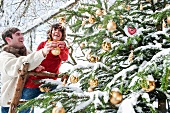 Young couple decorating Christmas tree in garden