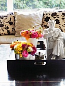 Bouquets in vases next to white china ornament on tray and coffee table in front of sofa with floral cushions