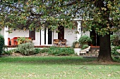 Autumnal garden in front of traditional house with columns on veranda