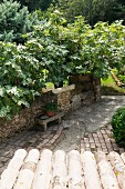 View across porch roof of stone bench against stone wall in Mediterranean garden