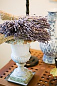 Dried lavender flowers and twigs resting on antique Greek vase on side table with perforated wooden top