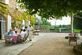 Guests taking breakfast on spacious terrace next to country house with view of Mediterranean garden