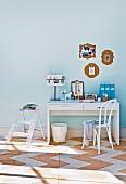 Kleiner weisser Schreibtisch & transparente Trittleiter als Ablage in hellblauen Raum mit Korkboden
