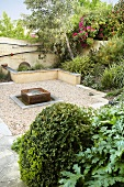 Relaxation area in lushly planted gravel garden with modern fountain