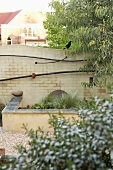 Curved brick wall with artistic decorations behind stone bench and raised bed