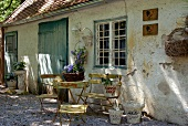 Iron garden furniture and nostalgic flower baskets against weathered facade