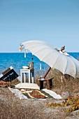 Seaside idyll - beach towel and stool on sandy ground below open parasol beside the sea