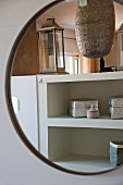 Decorative, Oriental metal boxes on shelves reflected in round mirror