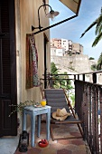 Simple, pale blue side table next to wooden deckchair with grey seat on small balcony of Mediterranean house with view of town on hillside