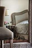 Large mirror with ornate frame on wall of feminine, elegant bedroom