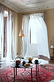 Grand interior with side tables on red Oriental rug and modern standard lamp in front of windows with fluttering, floor-length curtains