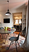 Bauhaus shell chairs on stone floor and retro pendant lamp above dining table in front of open doorway with view of kitchen beyond