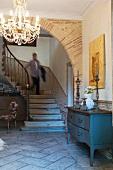 Holzkommode und Kronleuchter in einer Eingangshalle mit Rundbogen und Treppenaufgang