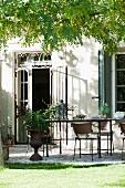 Terrassenplatz mit langem Tisch und Stühlen vor dem Haus unter Akazienbaum