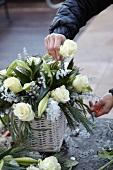 Hands placing white rose in almost-finished flower arrangement