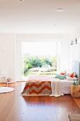 Bedroom with wooden floor and double bed in front of wide open patio doors