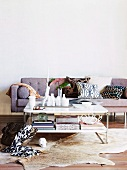 Sitting area in living room with sofa, animal fur rug and coffee table