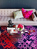 Sitting area in the living room with a gray sofa, carpet in shades of red and purple and a round glass table