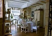 Mit einer Sammlung antiker Stühle, Kronleuchter und bodenlangem Tischtuch festlich gedeckte Tafel in einfach restauriertem Landhaus