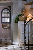 Foyer of old country house in shabby chic style with artistic metal staircase and original antique console table in background