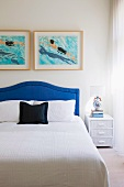 White bedspread on double bed with blue upholstered headboard below modern artworks on wall