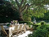Set table below tree in garden with fountain in background