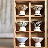 Assorted Sake Glasses on a Wooden Shelf