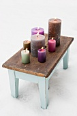A variety of colourful candles on old footstool in snow