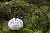 Contorted willow in spherical vase with crocheted cover
