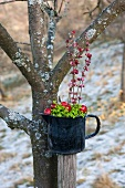Arrangement of moss, crab apples and pink snowberry flowers
