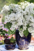 White lilac in blue vase outside on table