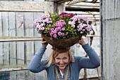 Frau hält lachend eine große Blumenschale auf dem Kopf